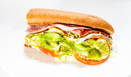 A fresh italian sub sandwich garnished with tomatoes, peppers and lettuce photo