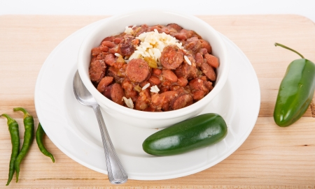 A bowl of red beans and rice with spicy, green jalapeno peppers photo