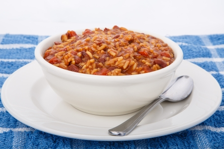A white bowl full of red beans and rice on blue towel with spoon photo