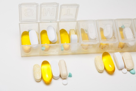 dosage: Daily dosage of pills going into a pill container Stock Photo