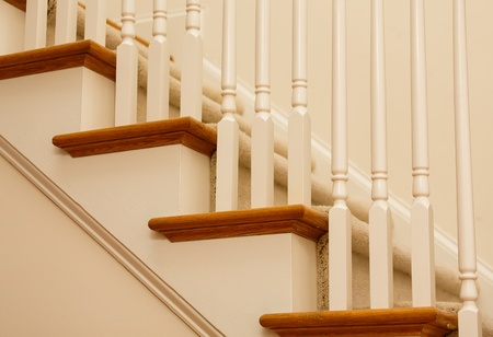 Details of an interior staircase with stained hardwood, painted pickets and carpet photo