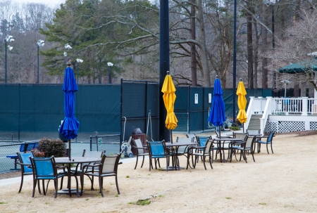 closed club: Closed tennis courts in winter with blue and yellow sun umbrellas