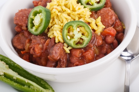 A bowl of red beans and yellow rice with cut jalapeno peppers photo