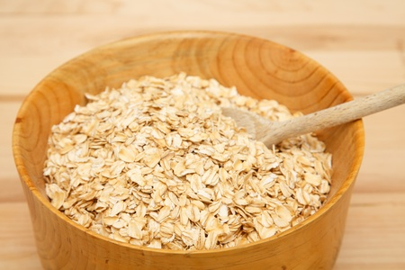 Dried, rolled oats in a wood bowl with wooden spoon on wood table photo