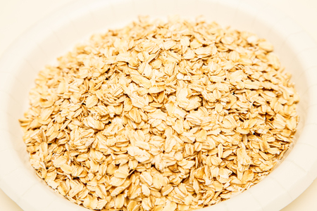 A white bowl full of dry rolled oats