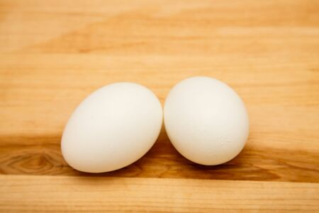 Two raw or boiled eggs on a wood cutting board Banque d'images
