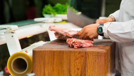 Butcher chopping meat on a wood block with cleaver showing motion blur Zdjęcie Seryjne