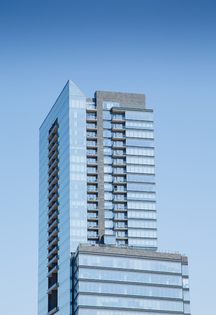 A tall, blue glass condominium tower with balconies under clear blue skies Stock Photo - 22543957