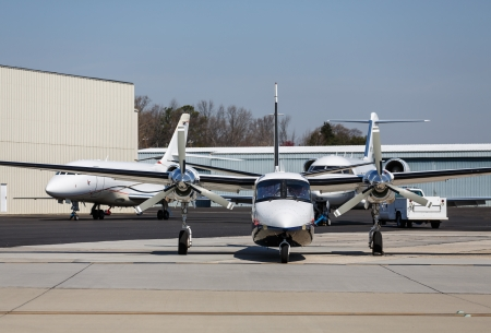 A large private turbo-prop airplane by hangers and private jets