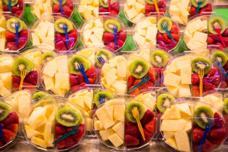 Clear plastic containers of strawberries, kiwi and pineapple with colorful plastic forks photo