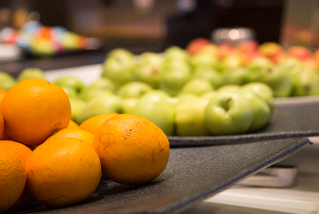 Fresh, whole oranges and apples on a fruit buffet