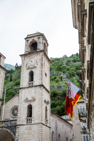 serbia: An ancient stone clock tower and flag in Kotor, Montenegro