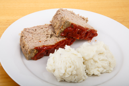 A serving of meatloaf and mashed potatoes on a white plate photo