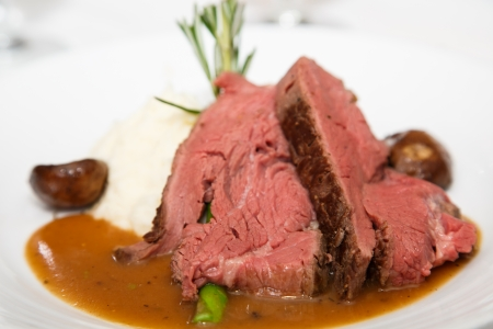 Slices of rare prime rib on a white plate with mushroom gravy, asparagus and a rosemary garnish