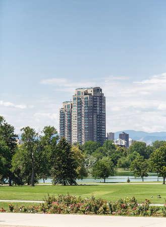 skyline of denver: A modern high rise condominium building rising into sky beyond a green park