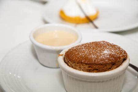 An individual chocolate souffle with a ramekin of vanilla sauce