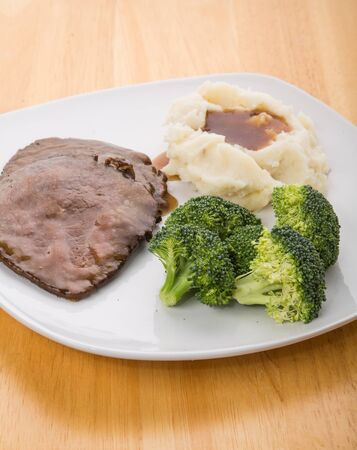 A dinner of sliced roast beef, mashed potatoes with gravy and fresh broccoli on a white plate on wood table. photo
