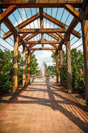 entrance arbor: A wood rose trellis over a brick sidewalk toward a fountain in a public garden Stock Photo