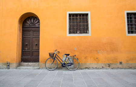 A bicycle leaning against an old plaster wall in Tuscany photo