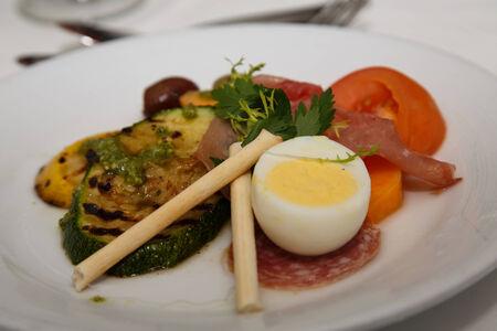 carnes y verduras: Un plato de verduras a la parrilla, embutidos y huevos duros para el aperitivo