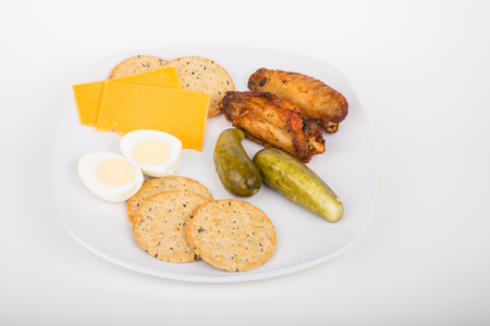 A plate of snacks, including sliced cheese, crackers, chicken wings, pickles and boiled egg photo