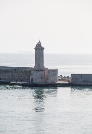 A stone block sea wall in the Mediterranean with a small lighthouse photo