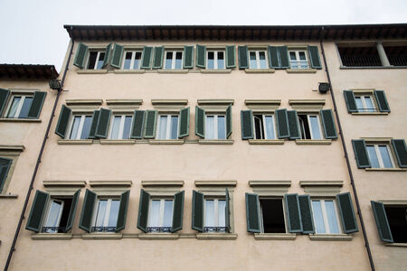 An old plaster hotel in Florence with green shuttes