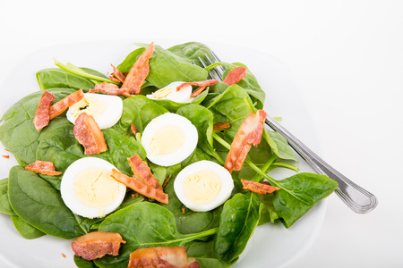 A fresh spinach salad with bacon and sliced, boiled eggs photo
