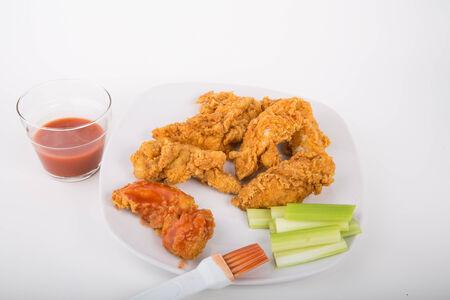 nuggets pollo: Tiras de pollo en un plato blanco con tiras de salsa picante de búfalo y apio
