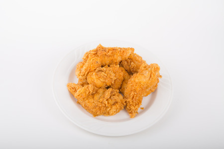 Fresh, hot, fried chicken strips on a white plate