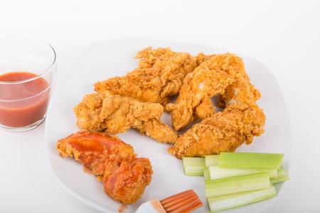 버팔로 핫 소스와 셀러리 스트립 하얀 접시에 치킨 스트립