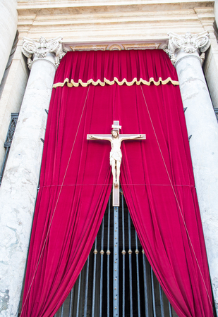 Statue of Jesus on the Cross by Red velvet curtain in the Vatican