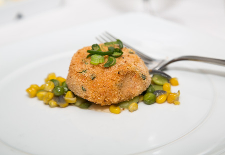 fritter: A conch fritter on white plate with corn relish and fork