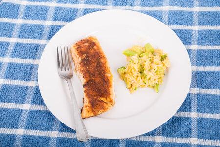 Een geroosterd zalmfilet op een witte plaat met broccoli en rijst braadpan