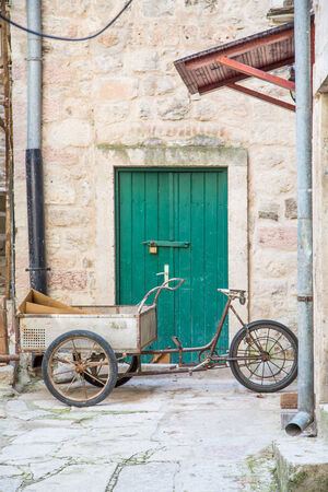 Old Three wheeled bicycle with cart by green door in old Kotor photo