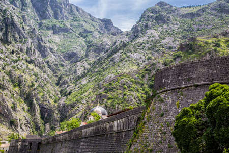 Church domes in Kotor over ancient wall under Montenegro mountain Stock fotó - 27085540