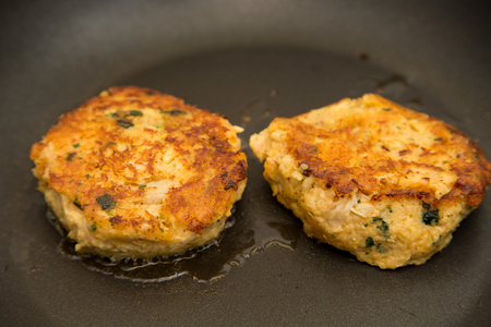 Two crab cakes sauteing in a frying pan with hot oil