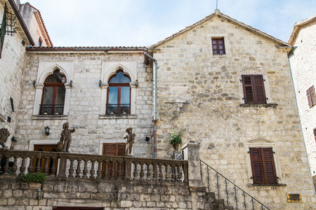 An old stone home in Kotor with statues on the balcony photo