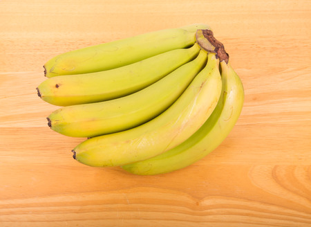 A bunch of green bananas on a wood table photo