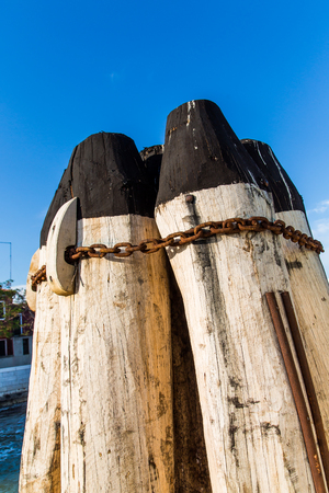 A rusty chain around old wooden posts on a pier under blue sky
