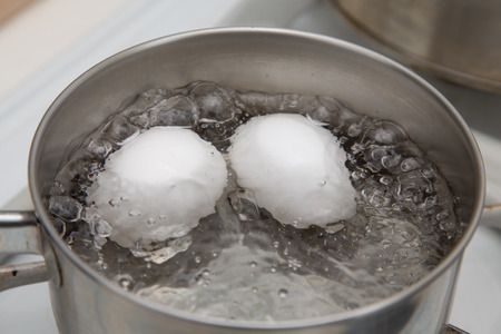 Two eggs boiling in  pan of water