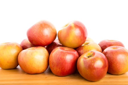 A bunch of fuji apples on a wood table with a white background Stock Photo
