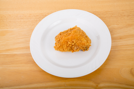 A piece of fresh, crunchy fried chicken on a white plate