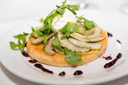 An appetizer of sliced fish on pita bread garnished with sour cream and arugula