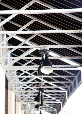 empty warehouse: Spotlights on Metal Beams Under Industrial Roof Stock Photo