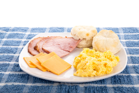 A hot, country breakfast of scrambled eggs, sliced ham, fresh, hot biscuits and sliced cheese Фото со стока