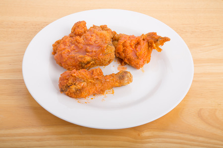 A plate of hot, crispy fried chicken with hot, spicy buffalo style sauce photo
