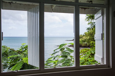 A view of the ocean in the tropics through an old wood window