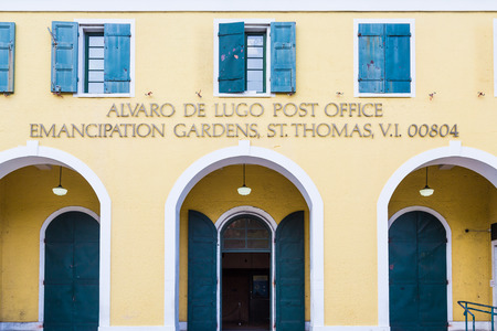 Old yellow plaster post office in St Thomas with blue shutters on doors and windows