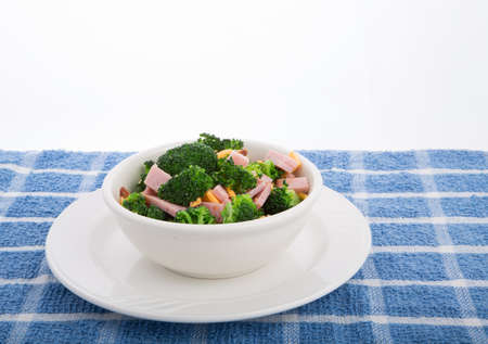 A fresh salad of green broccoli, sliced ham and grated cheddar cheese